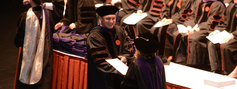 Photograph of a Brandeis School of Law student receiving his diploma from Dean Susan Duncan.