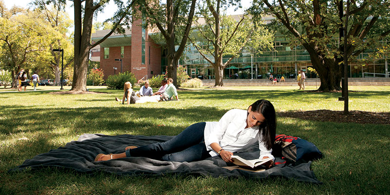 woman in blanket in grass reading in front of Ekstrom Library
