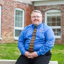 Aaron N. Coleman sitting on outdoor ledge