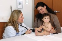Research practitioner working with a baby and his caregiver.