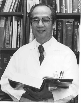 KC Huang, dressed in labcoat, stands in front of book case and holds a book open.