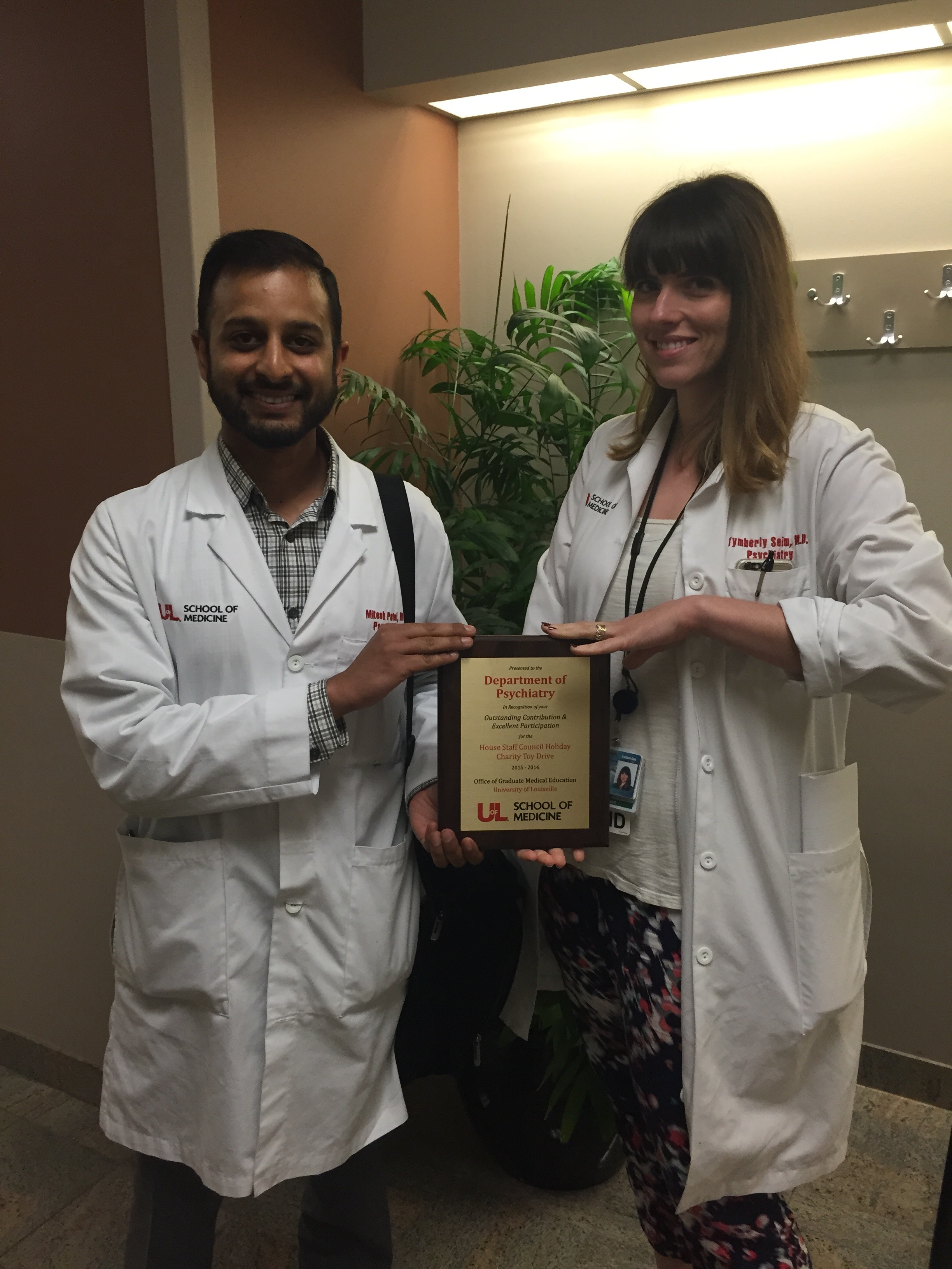 Mitesh Patel and Tymberly Siem hold the awards plaque for the most toys donated