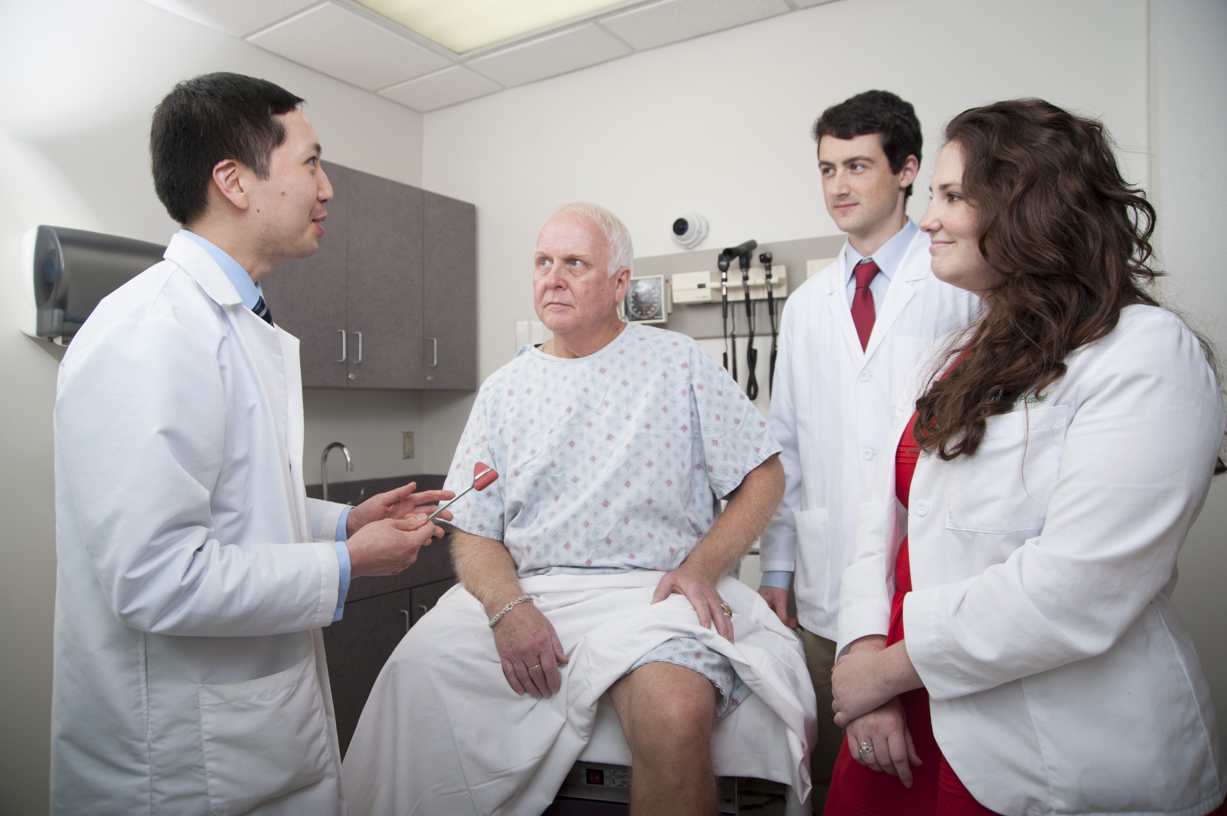 a faculty person teaches two students to examine the knee of a standardized patient