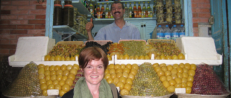 woman in front of middle east market fruit stand