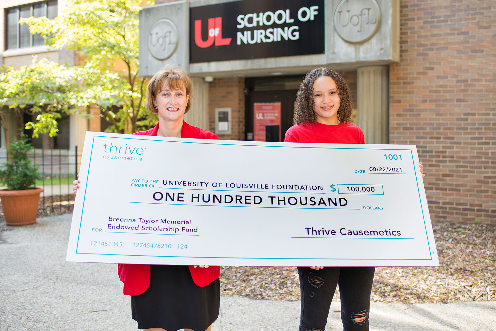 A wide angle picture of two women standing in front of the University of Louisville School of Nursing building. Freshman Kaelyn Goatley, has curly short brown hair and is wearing a red UofL shirt and black distressed jeans and School of Nursing Dean Sonya Hardin has short reddish brown hair and is wearing a red blazer and a black skirt. The pair are holding a check from Thrive Causemetics for the Breonna Taylor Memorial Endowed Scholarship fund in the amount of $100,000.