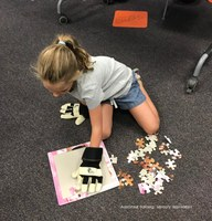 Girl wearing gardening gloves attempting to work jigsaw puzzle. Learning how astronauts must be able to function in space suits when working on International Space Station.