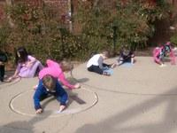 Kids chalk coloring planet models built into patio of the planetarium