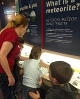 Kids and instructor looking at meteorite exhibit in planetarium lobby.