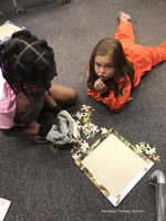 Child working a puzzle wearing gloves to simulate astronaut having to wear gloves when working in space.
