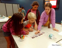 Team of 5-6th graders discussing important components to include in  Mars Outpost design.