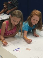 Two girls designing a lunar base using paper and markers.