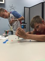 Kids working in pairs to perform an activity modeling using a robotic arm