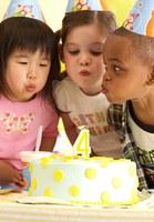 Three children celebrating a birthday.