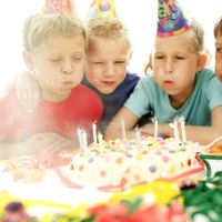 Kids blowing out candles on birthday cake.