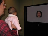 Father sitting with baby during face perception study.