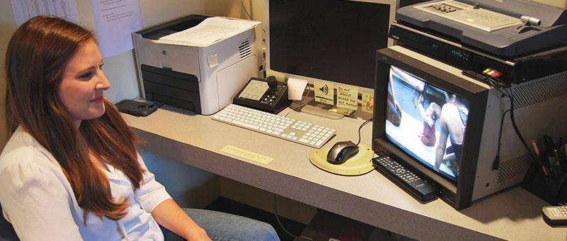 Student researcher looks at a monitor with infant subject on screen