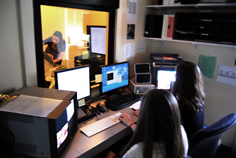 Two student researchers observe infant test from observation room