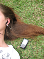 girl laying in grass with headphones and mp3 player.