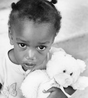 Children and effects of disaster image, small girl with stuffed animal, big eyes, black and white
