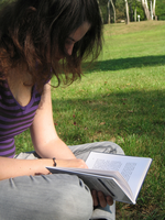 female student in purple reading book outside in the grass
