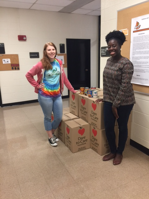 Two students posing with Dare to Care boxes