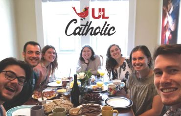 Students sitting around a dining table with a superimposed image of cardinal and the phrase U of L Catholic