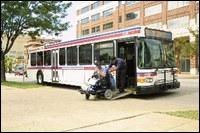 Wheelchair user exiting bus via deployed ramp