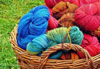 different colored skens of yarn gathered in a wicker basket