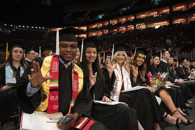 a group of new graduates holding up the L sign