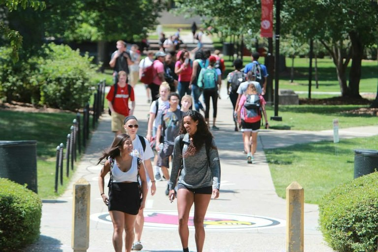 students walking on campus on a sunny day.