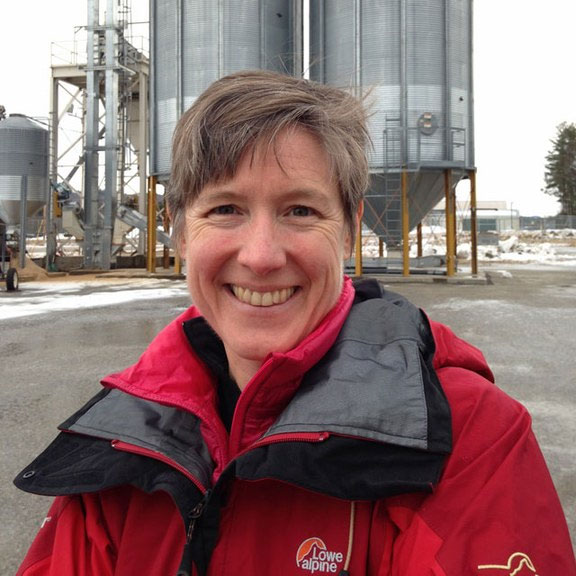 Dr. Katrina S. Korfmacher standing in front of silos