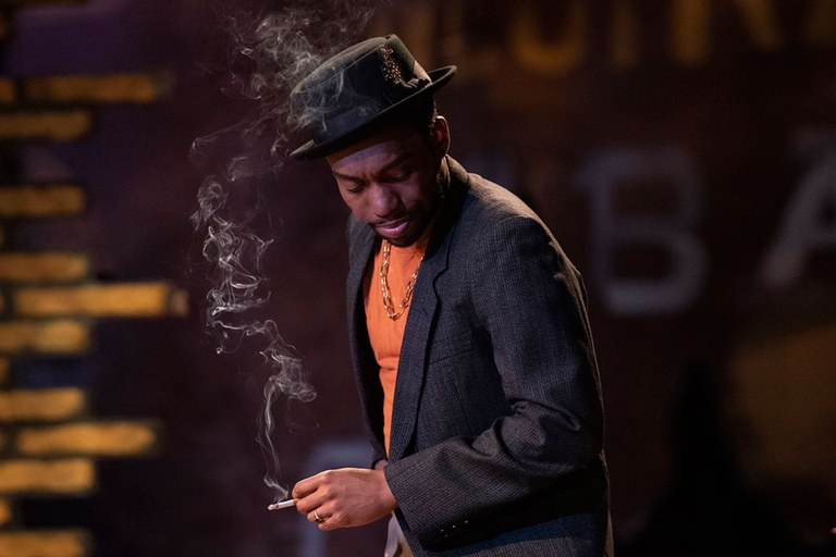 A man in a fedora and suit jacket smokes a cigarette