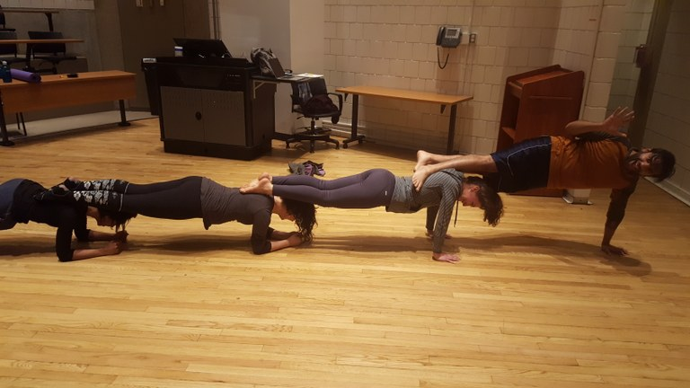 students exercising doing pushups as a group on each others shoulders